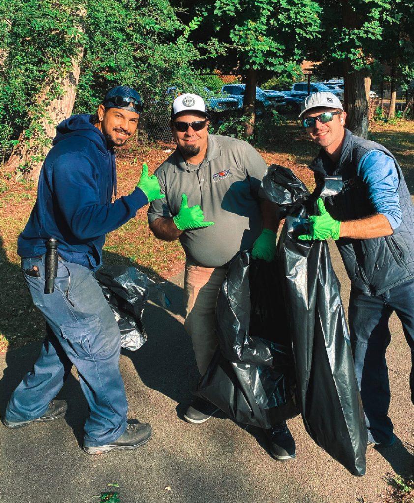 3 Fox Pest Control technicians gather trash